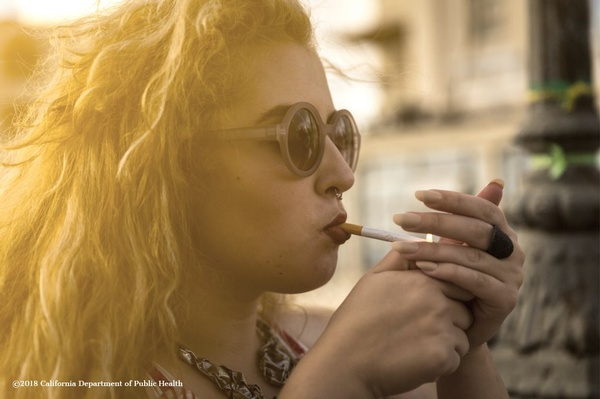 blonde-young-girl-woman-smoking-cigarette-and-relaxing-picture-id878347326.jpg